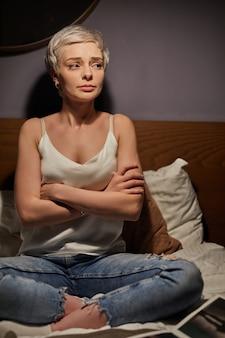 Mulher ansiosa e nervosa sentada na cama à noite com os braços cruzados, sofrendo de depressão, em desespero, preocupada com os problemas da vida. solidão, ansiedade