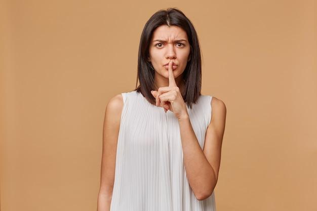 Mulher ansiosa, preocupada, preocupada, nervosa, em pânico, agressiva, raivosa demonstra um gesto de silêncio, segurando o dedo indicador perto da boca clama para que a privacidade seja mantida, em segredo, sobre a parede bege