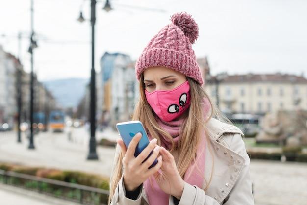 Mulher ansiosa usando máscara de coroa, verificando notícias em seu telefone