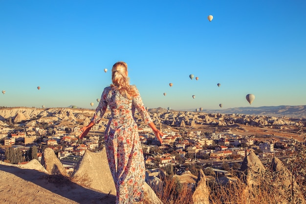 Mulher ao amanhecer, observando os balões e curtindo a vida.