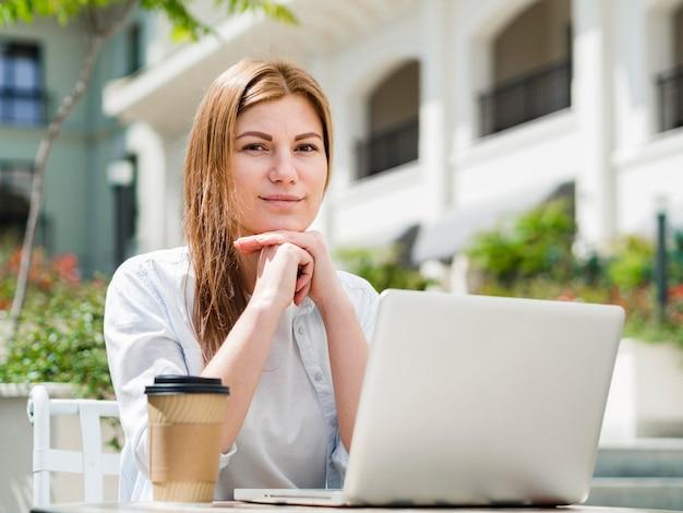 Mulher ao ar livre com café trabalhando no laptop