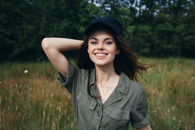 Mulher ao ar livre com um macacão verde e um boné preto com a mão atrás da cabeça sorrindo ar fresco close-up