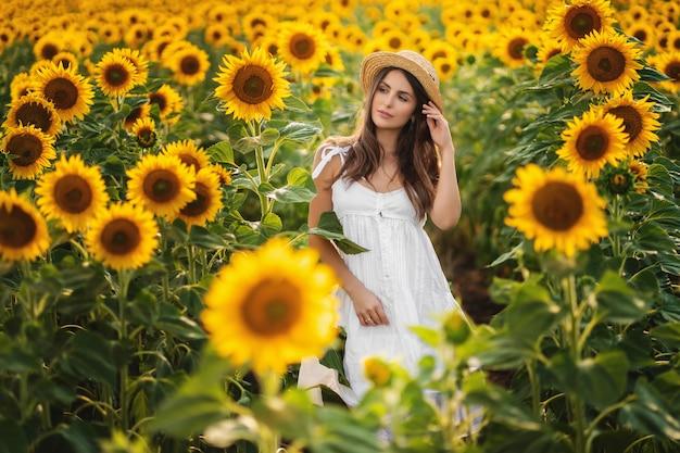Mulher ao ar livre curtindo a natureza. mulher linda modelo de vestido branco correndo no campo de verão.