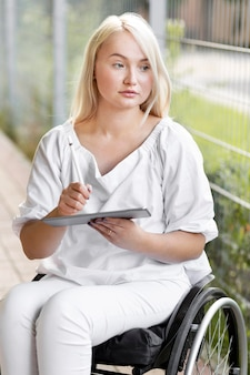 Mulher ao ar livre em cadeira de rodas com tablet