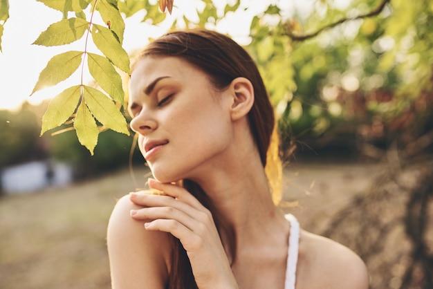 Mulher ao ar livre, folhas verdes, liberdade, lazer, estilo de vida. foto de alta qualidade