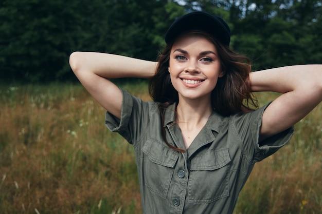 Mulher ao ar livre olhar para a frente sorriso com as mãos atrás da cabeça macacão verde verão close-up