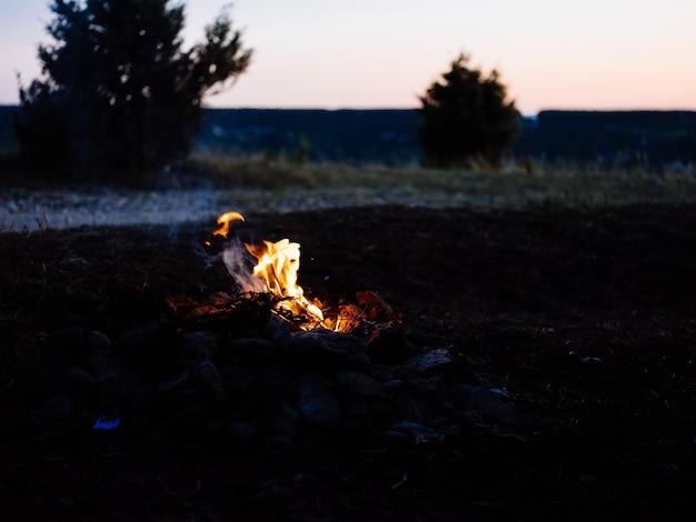 Mulher ao ar livre perto da fogueira, turismo na floresta, viagem