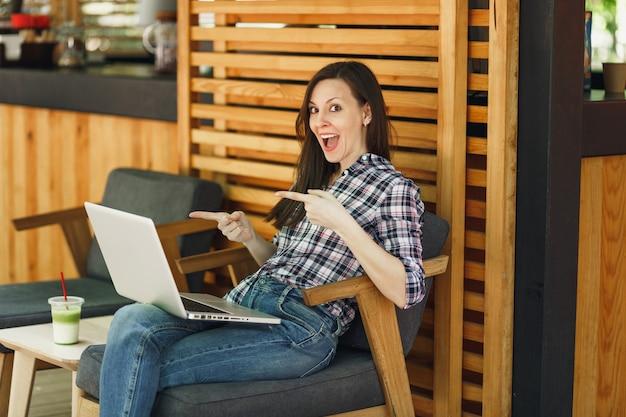 Mulher ao ar livre rua verão café loja de madeira café sentado em roupas casuais, trabalhando no computador laptop moderno, relaxando durante o tempo livre. escritório móvel