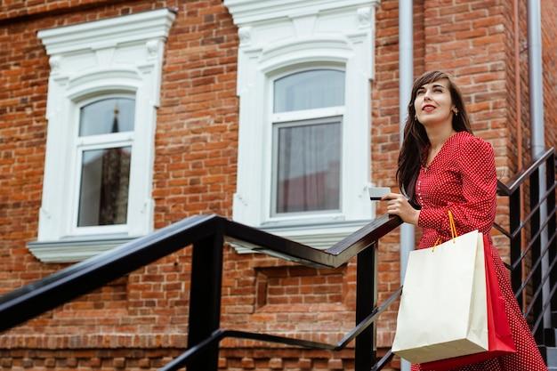 Mulher ao ar livre segurando um cartão de crédito e sacolas de compras