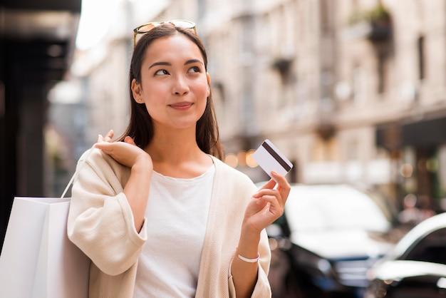 Mulher ao ar livre segurando um cartão de crédito e uma sacola de compras