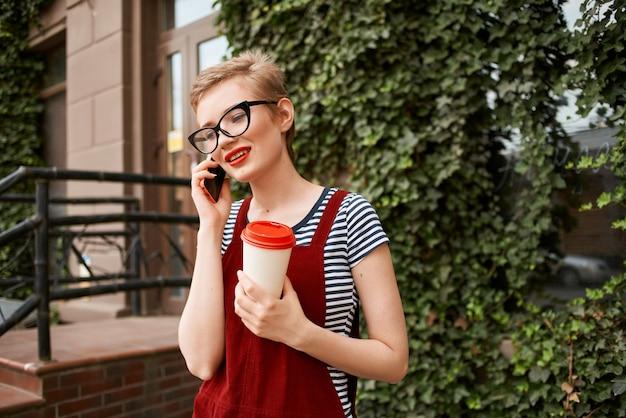 Mulher ao ar livre, uma xícara de café comunicação de férias de verão ao telefone