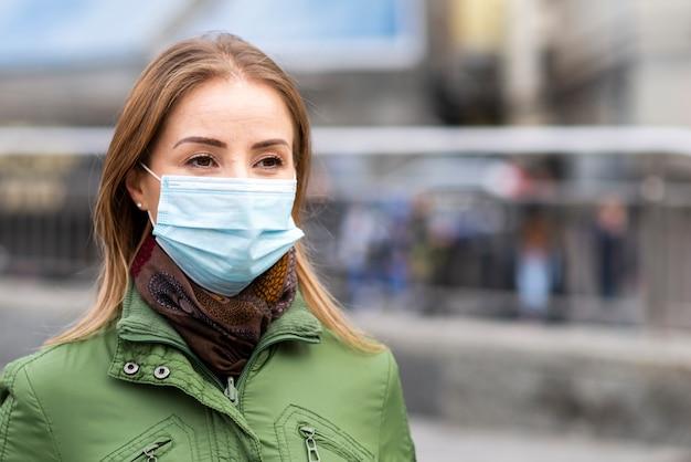 Mulher ao ar livre, vestindo uma máscara de proteção