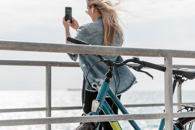 Mulher ao lado da bicicleta tirando uma foto