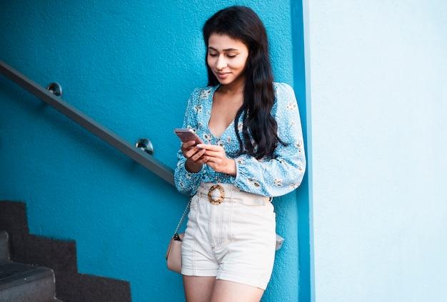Mulher ao lado da escada, olhando para o telefone