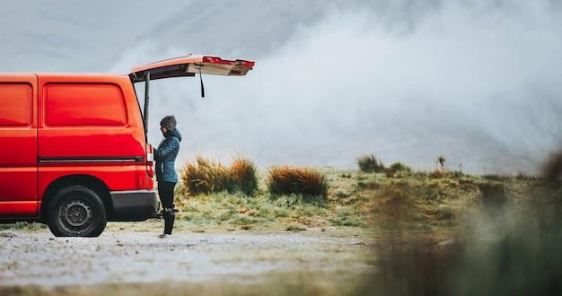 Mulher ao lado da van vermelha nas montanhas