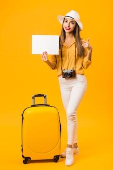 Mulher ao lado de bagagem posando enquanto aponta para o papel em branco que ela está segurando