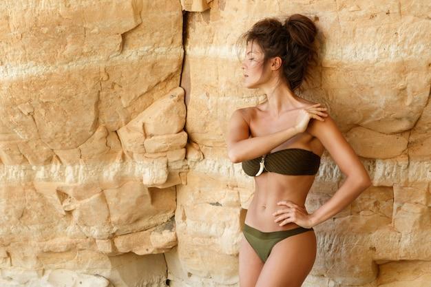 Mulher ao lado de penhascos de areia