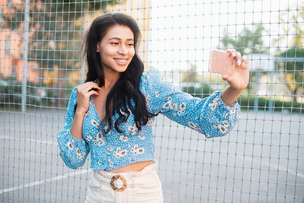 Mulher ao lado de um campo de basquete, tirando uma foto auto