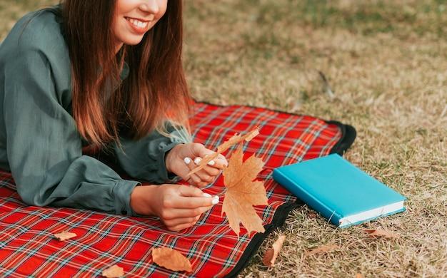Mulher ao lado de um livro em uma toalha de piquenique