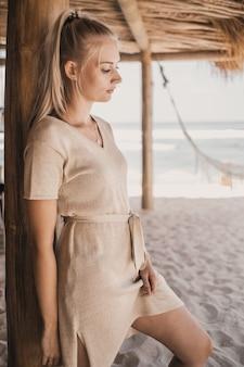 Mulher ao lado de uma coluna de madeira na areia