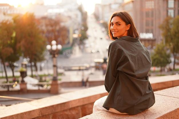 Mulher ao pôr do sol com vista incrível da cidade, curtindo dias quentes, liberdade, vibrações positivas