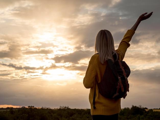 Mulher ao pôr do sol na montanha