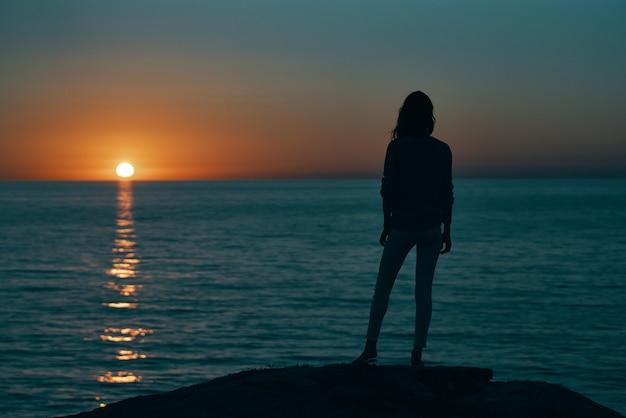 Mulher ao pôr do sol silhueta do mar na costa e no céu da praia