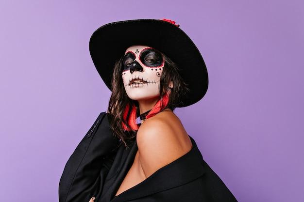 Mulher apaixonada de cabelos escuros com arte no rosto de halloween, segurando um chapéu preto.