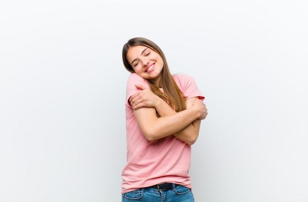 Mulher apaixonada, sorridente, abraçando e abraçando a si mesma, ficando solteira, sendo egoísta e egocêntrica