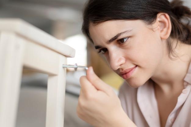Mulher aparafusando o prego de uma cadeira para mobília pronta para montar