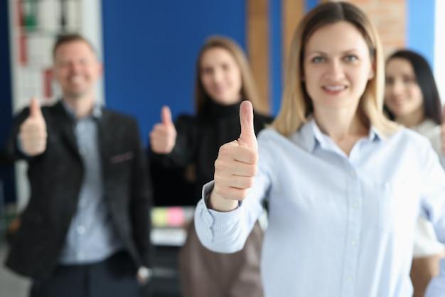 Mulher aparecendo o polegar da equipe de colegas em close-up