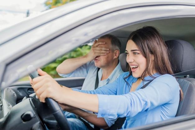 Mulher apavorada apertando o pedal do freio e grita de medo ou frustração.