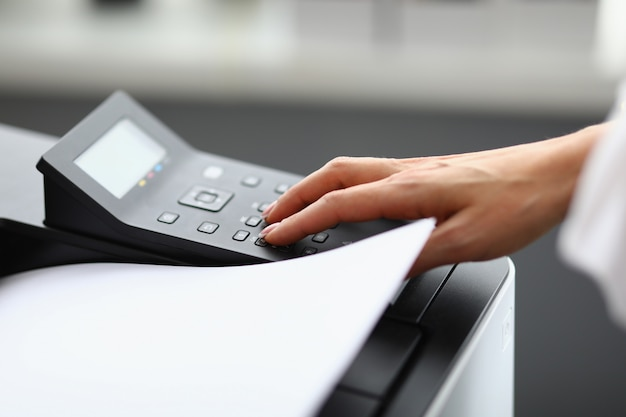 Mulher aperta botões na impressora de perto