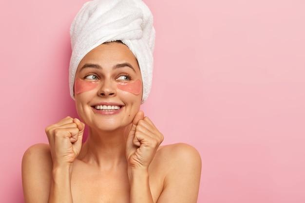 Mulher aperta os dentes e os punhos, desvia o olhar com expressão de alegria, usa uma toalha branca macia na cabeça, tem ombros nus