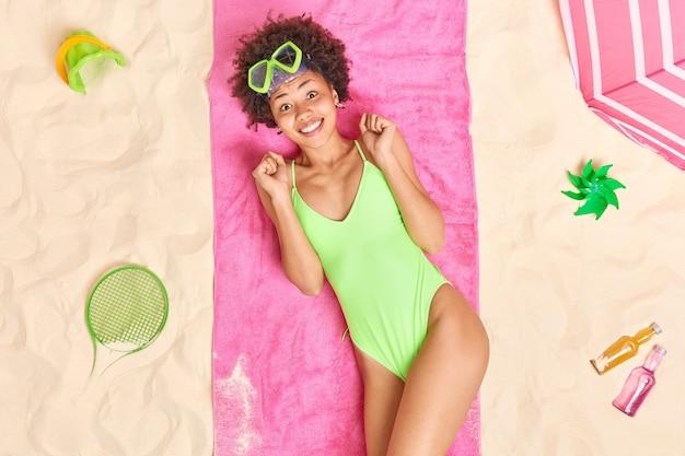 Mulher aperta os punhos alegra sucesso usa máscara de mergulho e biquíni verde encontra-se na toalha rosa na praia de areia goza de férias de verão se bronzear à beira-mar. conceito de férias