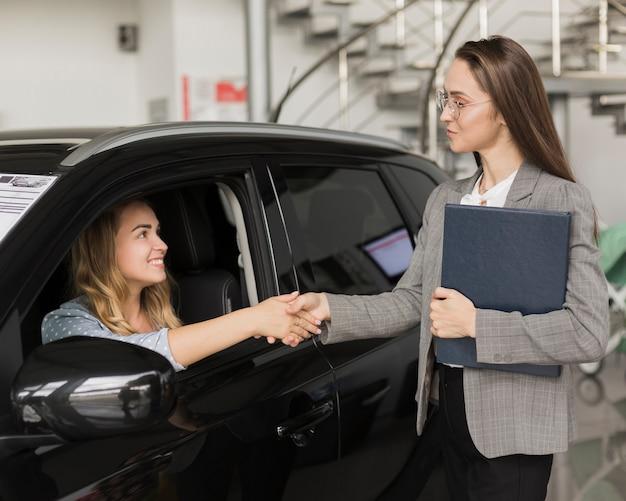 Mulher, apertar mão, com, negociante carro