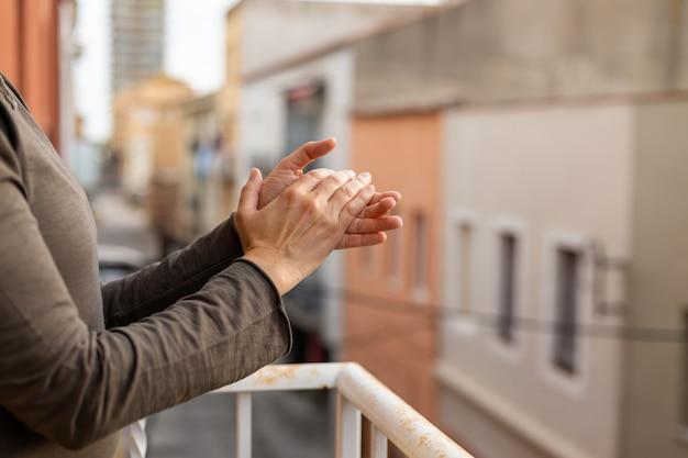 Mulher aplaudindo em uma varanda da espanha saudação por trabalhos de médicos, enfermeiros, políticas durante a epidemia de coronavírus