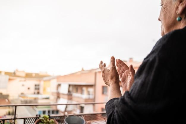 Mulher aplaudindo por parabenizar os profissionais de saúde durante a crise de coronavírus