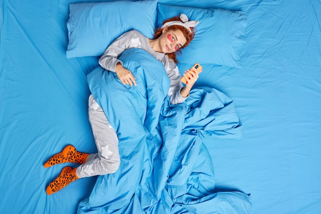 Mulher aplica adesivos sob os olhos passa por procedimentos de beleza vestida com pijama confortável usa smartphone cônico com cobertor