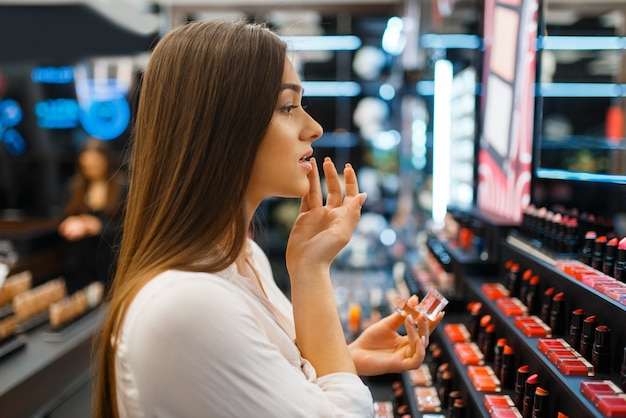 Mulher aplica batom em loja de cosméticos. comprador em vitrine em salão de beleza de luxo, cliente mulher no mercado de moda