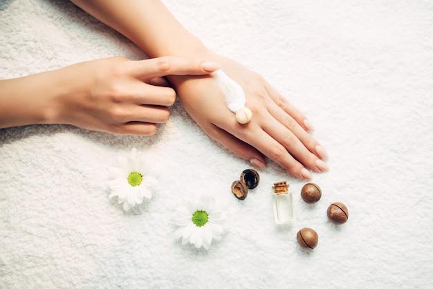 Mulher aplica creme natural na mão