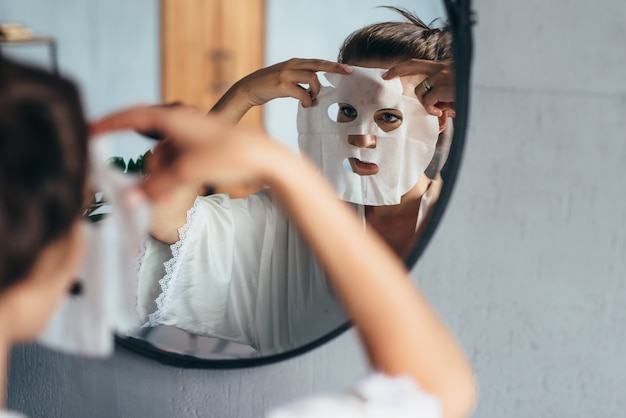 Mulher aplica lençol de máscara no rosto se olhando no espelho