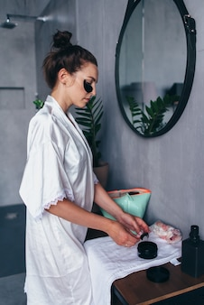 Mulher aplica manchas na pele sob os olhos.