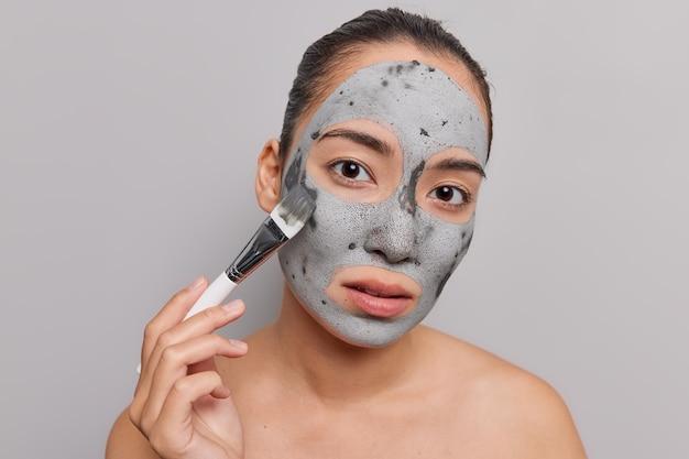 Mulher aplica máscara de argila purificadora no rosto com escova cosmética aprecia tratamento de pele olha diretamente para modelos de câmeras nuas em cinza