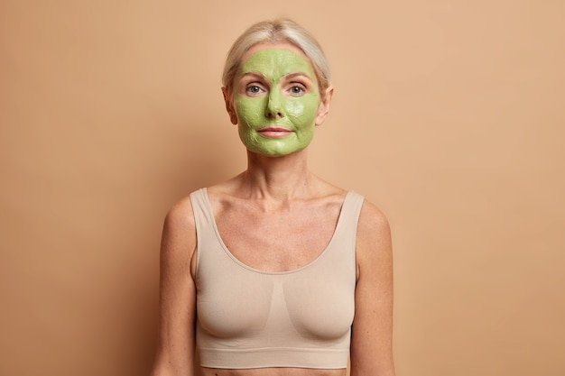 Mulher aplica máscara facial nutritiva verde usa produtos cosméticos