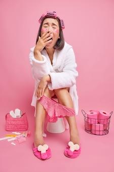Mulher aplica rolos de cabelo patches de beleza usa roupão de banho branco calcinha de renda rosa senta no vaso sanitário sob a pele procedimentos de cuidados com a pele se prepara para poses de festa no banheiro sozinho