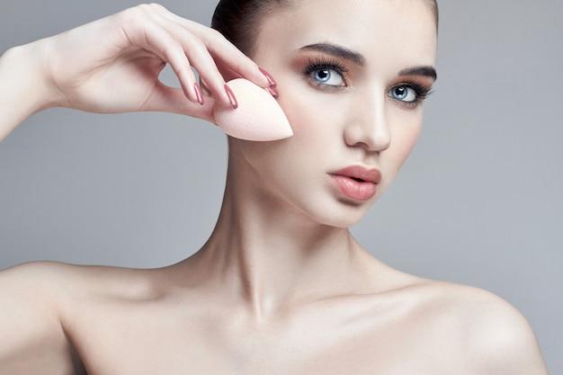 Mulher aplicada com uma maquiagem de esponja no rosto