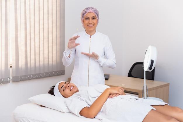 Mulher aplicando ácido hialurônico no rosto. esteticista segurando uma seringa com ácido hialurônico e paciente em segundo plano.
