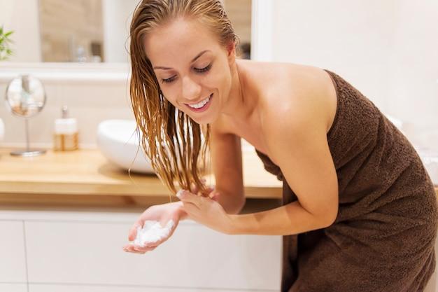 Mulher aplicando condicionador após o banho