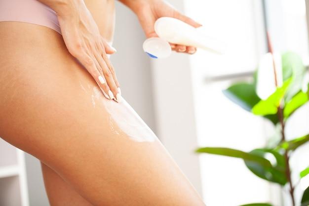 Mulher aplicando creme cosmético de celulite na perna.